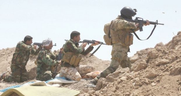 Iraqi soldiers and Shiite fighters from the popular committees hold a post as they fire towards Islamic State (IS) group positions in the Garma district of Anbar province west of the Iraqi capital Baghdad, on May 19, 2015.  Iraq's army and allied paramilitary forces massed around Anbar's provincial capital Ramadi, looking for swift action to recapture the city from the Islamic State group before it builds up defences. AFP PHOTO / AHMAD AL-RUBAYE