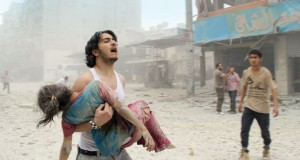 TOPSHOTS -- AFP PICTURES OF THE YEAR 2014 -- A man carries a young girl who was injured in a reported barrel-bomb attack by government forces on June 3, 2014 in Kallaseh district in the northern city of Aleppo. Some 2,000 civilians, including more than 500 children, have been killed in regime air strikes on rebel-held areas of Aleppo since January, many of them in barrel bomb attacks. AFP PHOTO / BARAA AL-HALABI